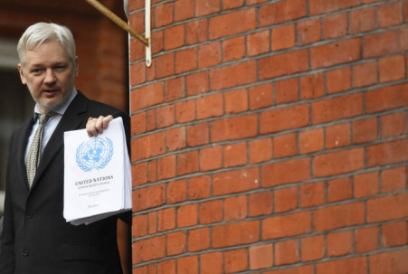 WikiLeaks founder Julian Assange holds a copy of a UN ruling as he makes a speech from the balcony of the Ecuadorian Embassy, in London, February 5, 2016.