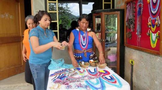 Lorena Chamba (izq.) compró los collares y aretes de plumas a Isabel Acacho (der.)