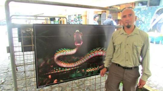 Darwin Núñez, junto a una fotografía de serpiente tomada en una de sus expediciones. Foto: La Hora