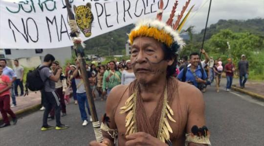 """Con un gran cartel con la leyenda """"La selva es nuestra vida. No más petróleo"""", la caminata llegó hasta la unidad judicial de Puyo para el inicio de una audiencia. Foto: El Comercio"""