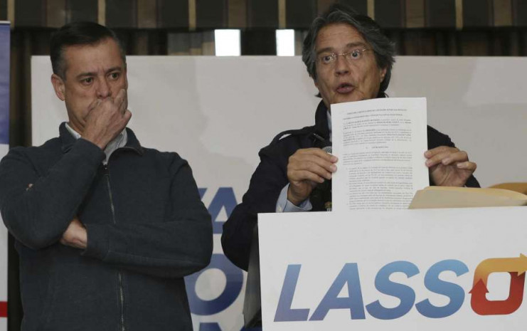Guillermo Lasso, the opposition candidate defeated in the elections of April 2, shows a document during a press conference at Dan Carlton hotel in Quito, Ecuador, Wednesday, April 12, 2017.