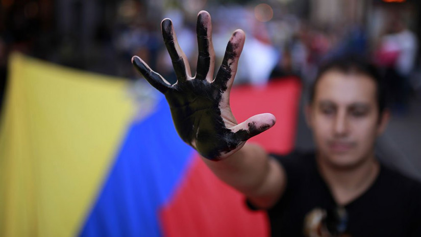 A protester shows his black-painted hand as he carries an Ecuador flag to protest against Chevron and the oil contamination in Ecuador's Amazon region during a demonstration in Madrid, Spain, in 2013. Ecuador was awarded a $19 billion judgment for damages in 2013, but that was subsequently overturned due to illegal activity by the plaintiffs' U.S.-based attorney. Photo: Investor's Business Daily
