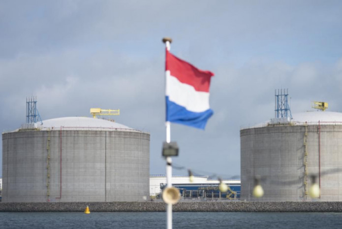 The Dutch national flag flies from a tour boat as liquid natural gas (LNG) silos stand on the shore at the Port of Rotterdam, Netherlands. Photo: Forbes