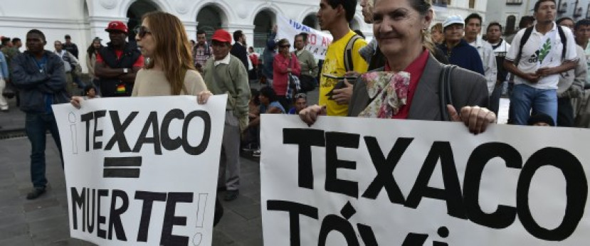Activists holds signs reading 'Texaco = Death' and 'Texaco = Toxic' as they protest against US multinational energy corporation Chevron at a square in Quito on May 21, 2014. Lawyers for a group of Ecuadoran villagers are asking Canada's high court on Thursday to grant their clients access to Canadian courts to enforce a US$9.5-billion Ecuadorian judgment against Chevron Corp for rainforest damage. | RODRIGO BUENDIA via Getty Images
