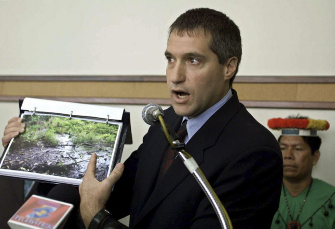 Attorney Steven Donziger shows pictures of a pool of oil which seeped out from an oil waste pit left behind by Texaco at an oil pump site in the Amazon jungle, in Quito, in this October 30, 2003 file photo.  Foto: Yahoo Finance