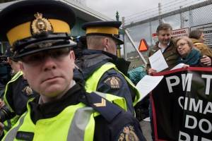 An RCMP officer reads a court order to Federal Green Party Leader Elizabeth May, right, and NDP MP Kennedy Stewart, second right, before they were arrested after joining protesters outside Kinder Morgan's facility in Burnaby, B.C., on Friday March 23, 2018. Photo: Toronto Sun