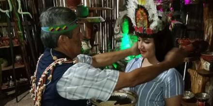 Un guía de Madre Tierra atavía a las turistas con elementos propios de su vestimenta, como coronas de plumas. Foto: El Telégrafo
